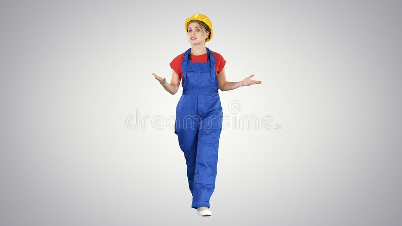 Cheerful female construction worker talking to camera on gradient background. stock photo