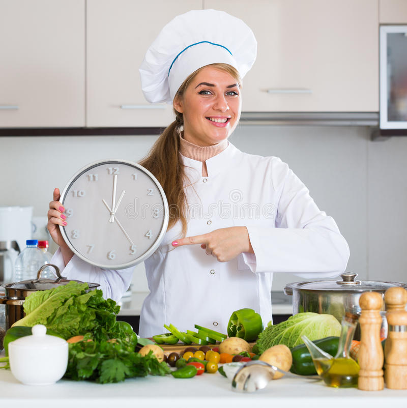 Cheerful female cook with clock and vegetables in kitchen stock photography