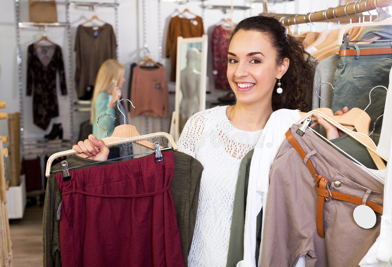 Cheerful female customer selecting new garments. Smiling female customer selecting new garments at the store royalty free stock photo