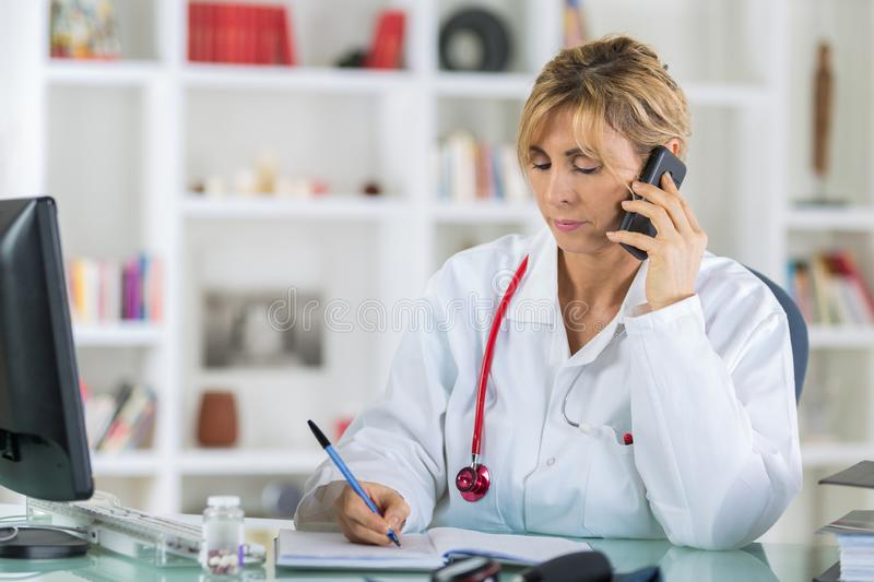 Cheerful female doctor on phone at office. Female royalty free stock photos