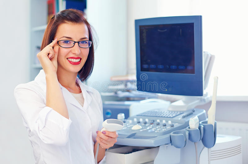 Cheerful female doctor with ultrasound sensor. Cheerful young female doctor with ultrasound sensor royalty free stock images