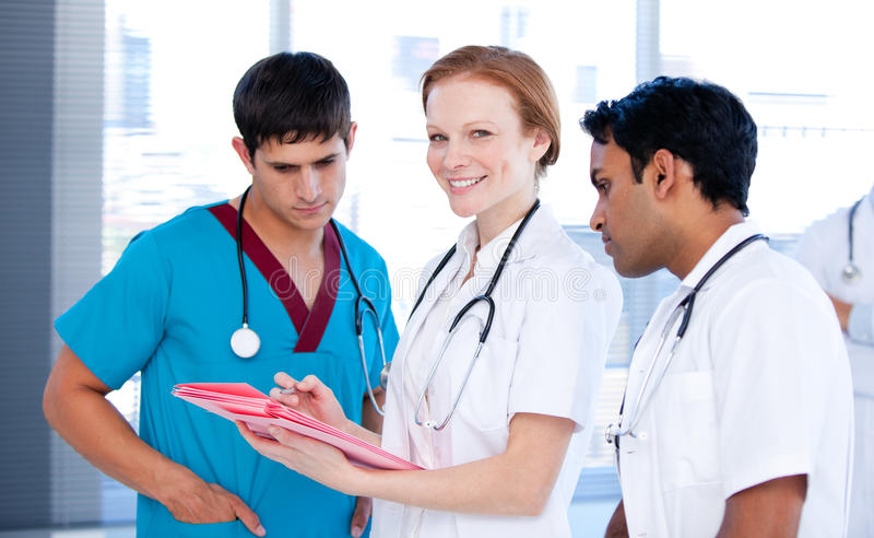 Cheerful female doctor working with her team stock photo