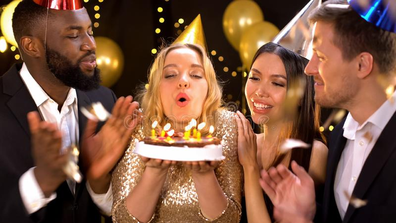 Cheerful female enjoying birthday with close friends, blowing out cake candles royalty free stock images