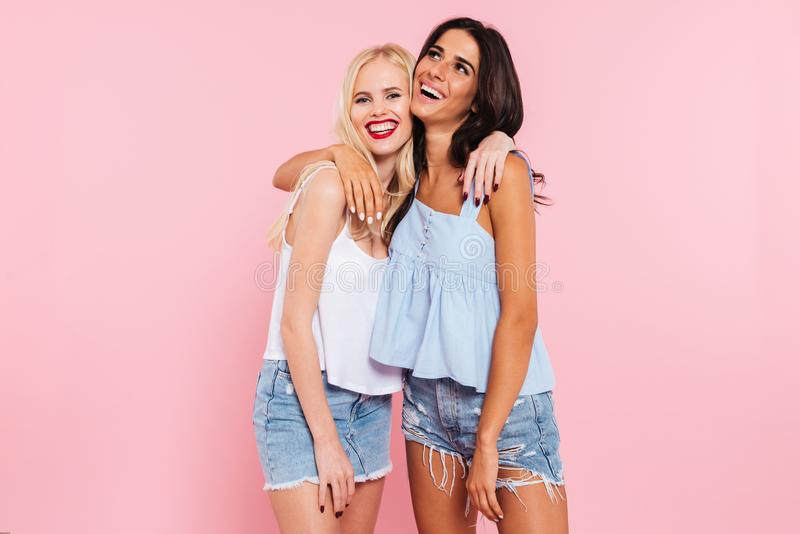 Cheerful female friends hugging and laughing to camera stock photos