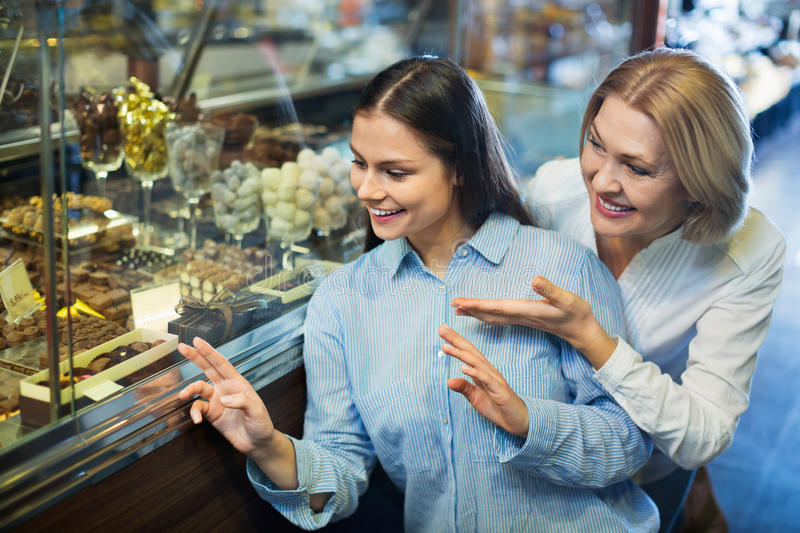 Cheerful female friends selecting fine chocolates and confection stock photography