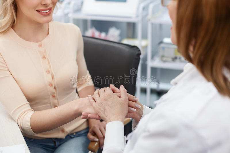 Cheerful female general practitioner talking with lady stock photography