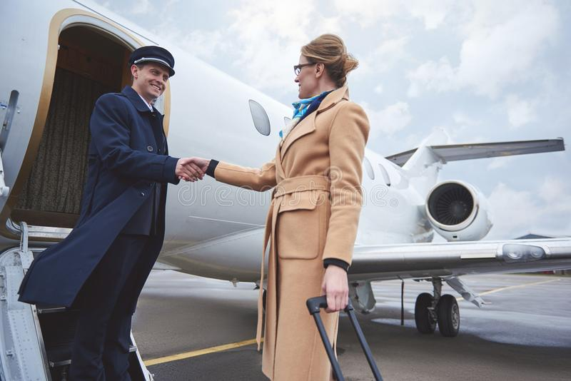 Outgoing businesswoman welcoming with pilot royalty free stock image