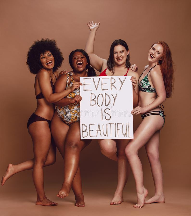 Cheerful female group with every body is beautiful signboard. Cheerful group of women holding a every body is beautiful signboard over brown background stock photos