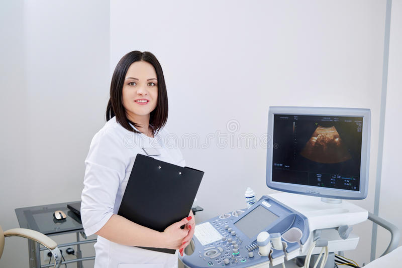 Cheerful female gynecologist posing at her office royalty free stock photography