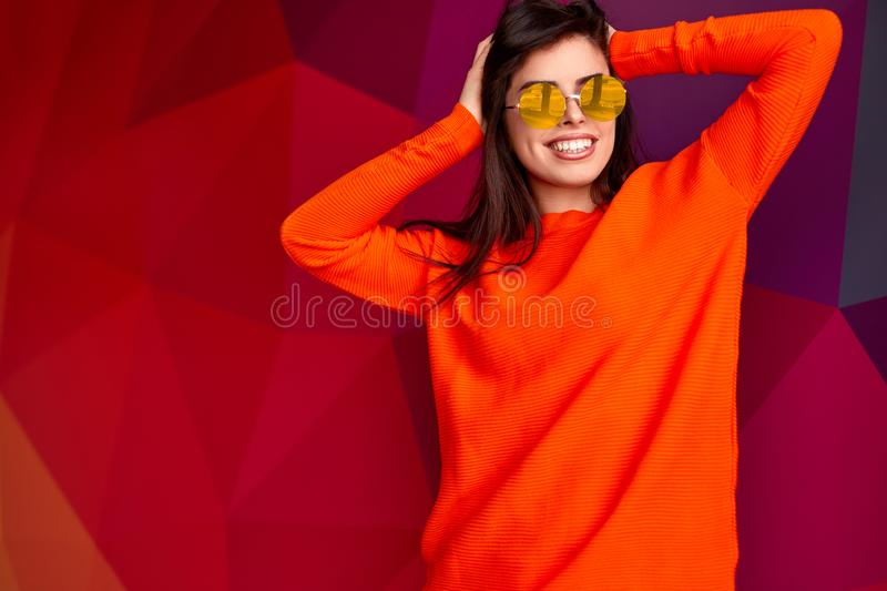 Cheerful female hipster rumpling hair. Happy young woman in orange cardigan and trendy sunglasses smiling and looking away while rumpling hair against geometric royalty free stock photo