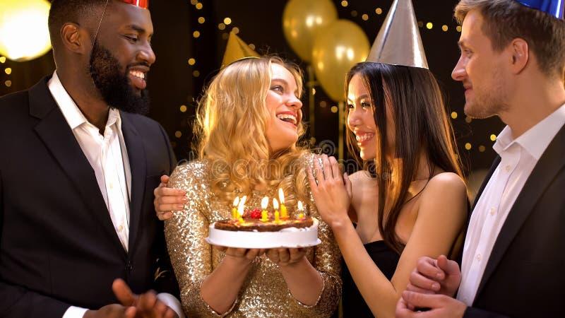 Cheerful female holding birthday cake preparing to blow candles, friends around stock photo