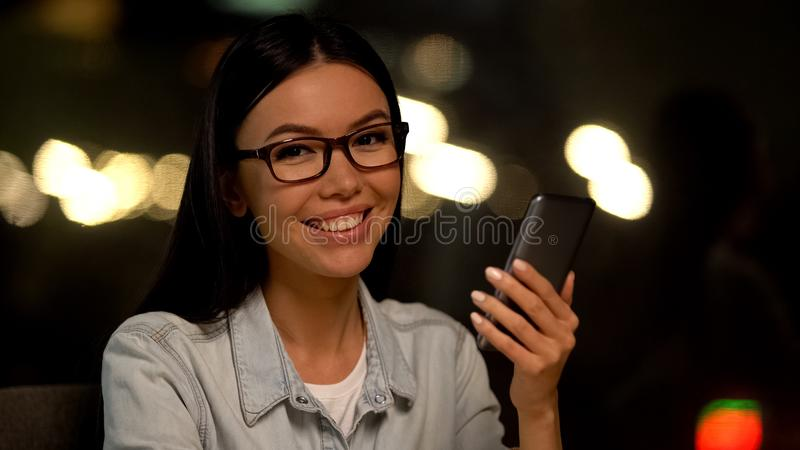 Cheerful female holding mobile in hand, online communication, modern technology royalty free stock images