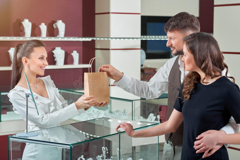 Cheerful female jeweler handing purchase in a shopping bag to he royalty free stock photos