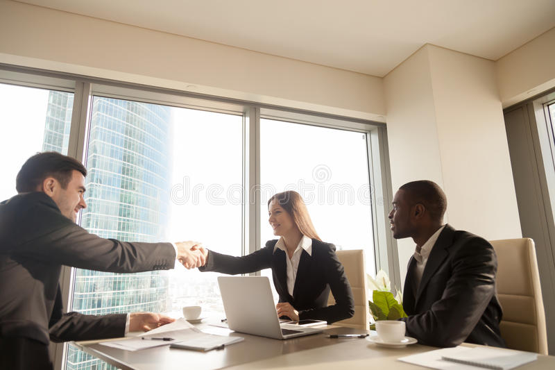 Cheerful female and male caucasian partners handshaking at multi. Cheerful female and male caucasian partners handshaking over office desk, multi-ethnic meeting royalty free stock photo