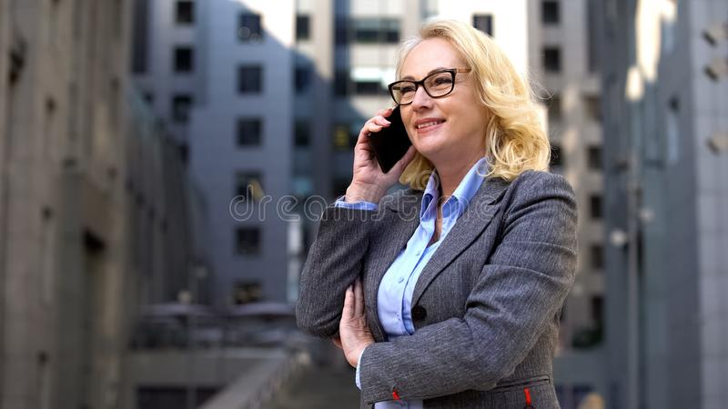 Cheerful female manager talking on phone standing outside, client communication royalty free stock photography