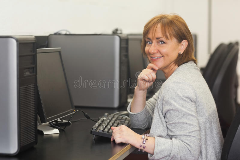 Download Cheerful Female Mature Student Sitting In Computer Class Stock Photo - Image: 35781544