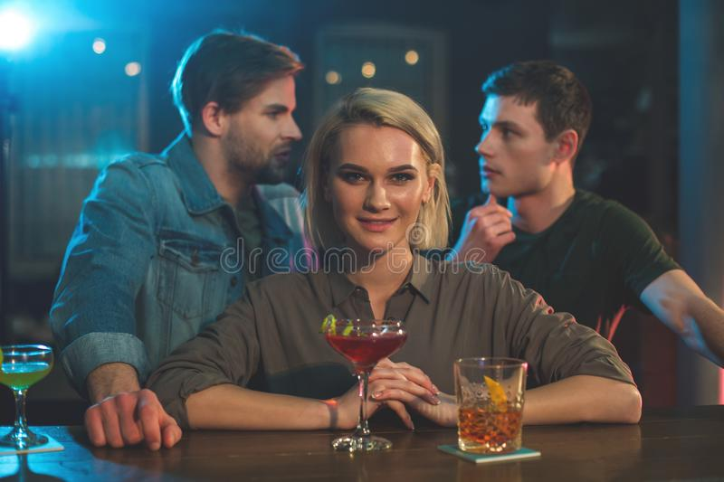 Cheerful female and men in bar. Happy lady tasting cocktail at counter. Two males telling while standing opposite her. Competition in club concept royalty free stock photo