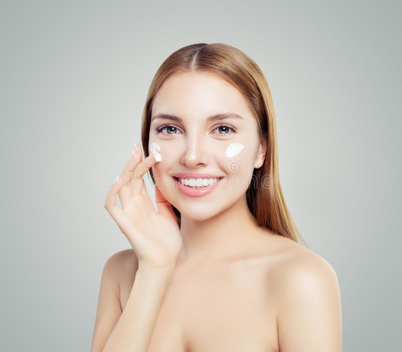 Cheerful female model applying anti-aging cream on her face. Skin care, beauty and facial treatment concept royalty free stock image