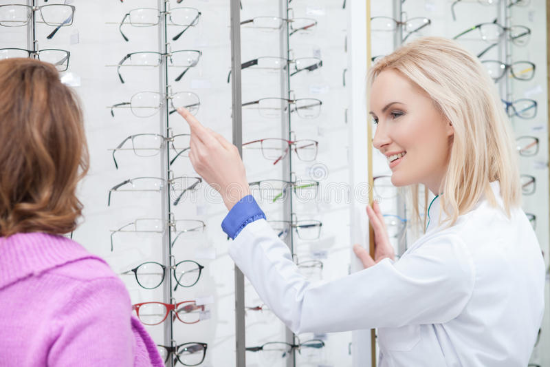 Cheerful female optometrist is consulting mature lady. Try on these spectacles. Professional optician is helping the senior women to choose new eyeglasses. She stock photo