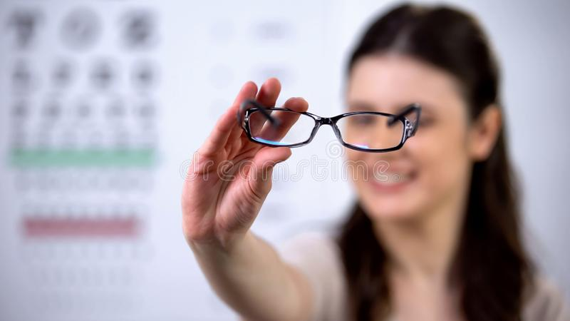 Cheerful female optometrist patient showing new eyeglasses, sight correction royalty free stock photo