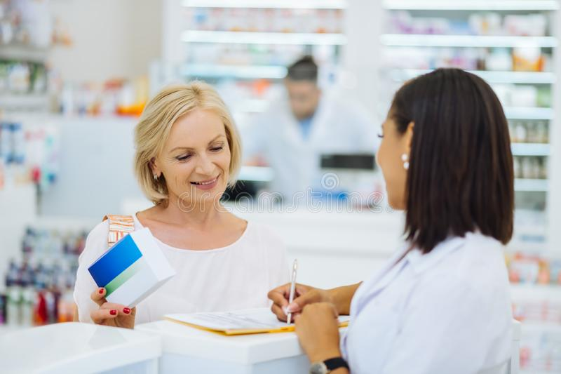 Cheerful female person buying her favorite vitamins royalty free stock photography