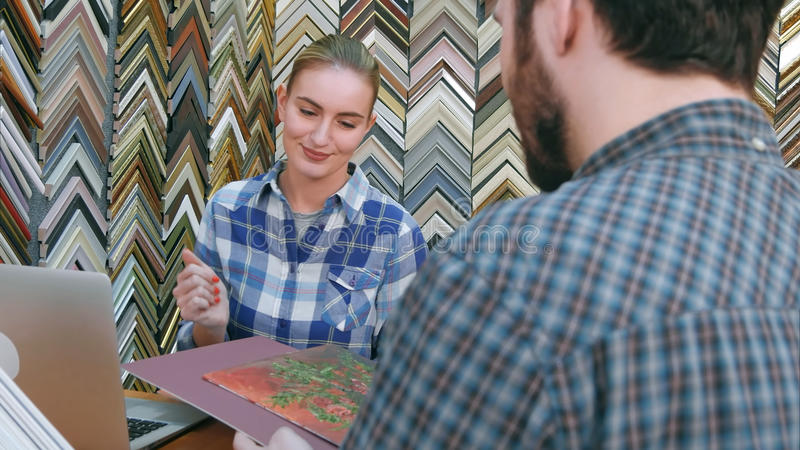 Cheerful female seller helping customer with frame and passepartout for his painting in store. Close up. Professional shot in 4K resolution. 083. You can use stock photography