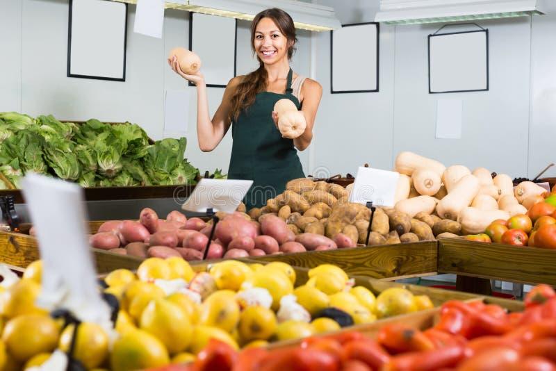 Cheerful female seller holding yellow gourd. Cheerful female seller wearing apron holding yellow gourd on market stock photos