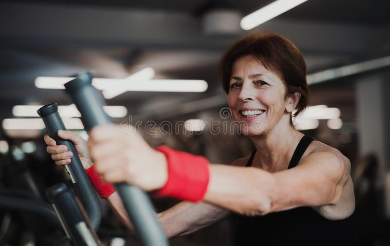 A cheerful female senior in gym doing cardio workout. royalty free stock photo