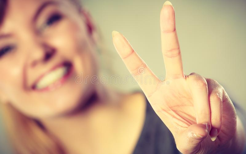 Cheerful female shows victory symbol. Good feeling and positive emotions of win. Cheerful happy female shows two fingers as symbol of victory and won royalty free stock images