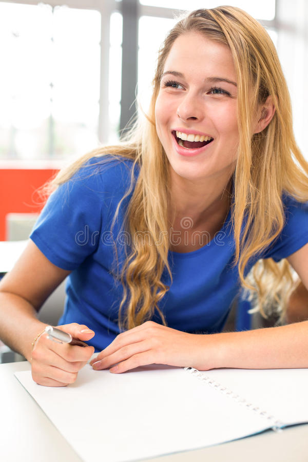 Cheerful female student writing notes in classroom royalty free stock images