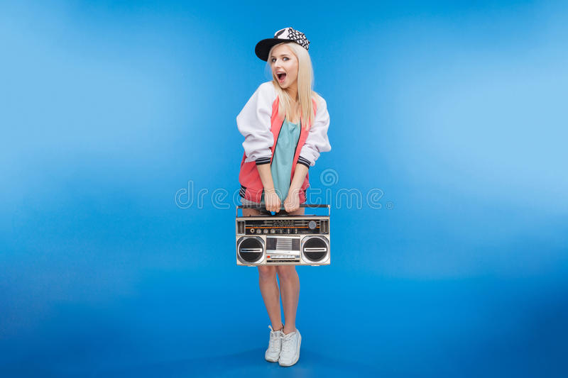 Cheerful female teenager holding retro boom box. Full length portrait of a cheerful female teenager holding retro boom box on blue background royalty free stock image