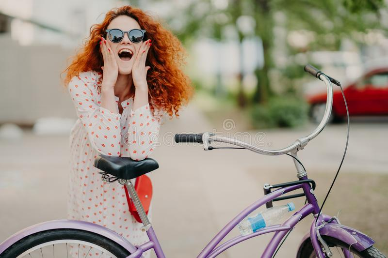 Cheerful female urban biker wears sunglasses and dress, has luxurious crisp foxy hair, keeps elbows on saddle of bicycle, spends royalty free stock image