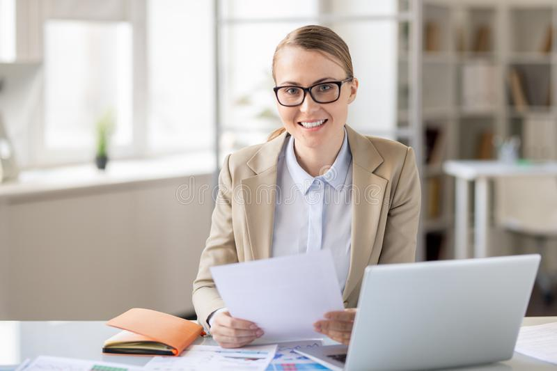 Cheerful financial employee examining report royalty free stock images