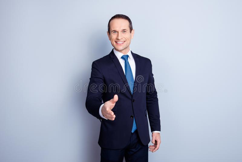 Cheerful financier, positive economist, corporate, responsible p. Olitic man in formalwear with tie offering hand for shaking, having a deal, standing over gray royalty free stock photo