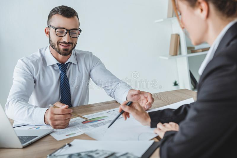 Cheerful financiers pointing on documents. In office royalty free stock photo