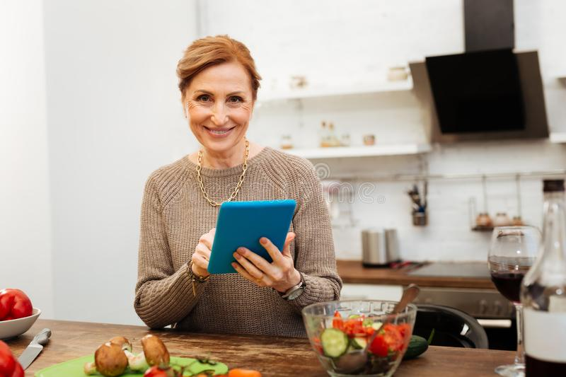 Cheerful fit mature lady smiling while checking information stock photos