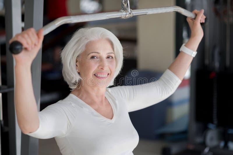 Cheerful fit senior woman keeping . stock photos
