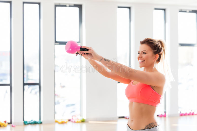 Cheerful, fit woman doing a kettlebell swing. stock photo
