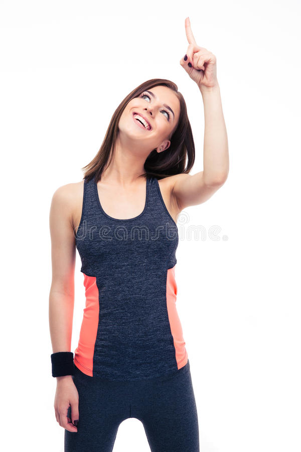 Cheerful fitness woman in sportswear pointing up royalty free stock photography