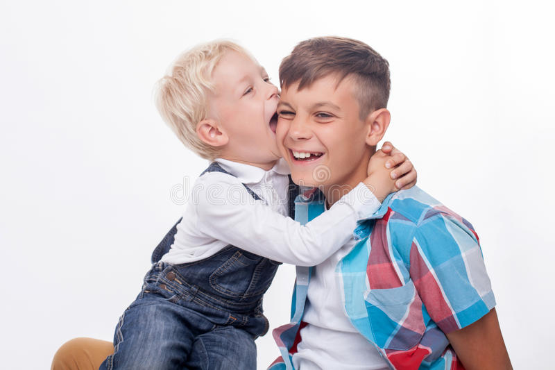 Cheerful friendly brothers are making fun together. Cute two boys are playing and laughing. The elder boy is holding his little brother on knees. The small child royalty free stock photo