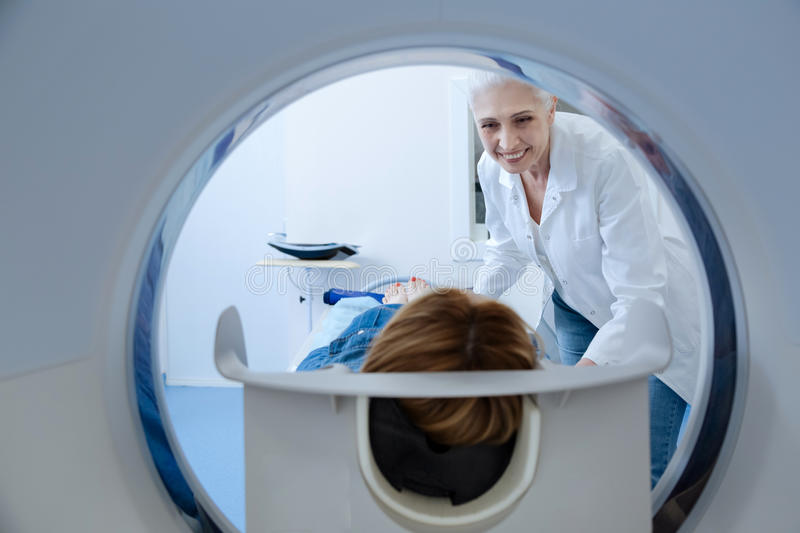 Cheerful friendly doctor preparing a patient to examination stock photos