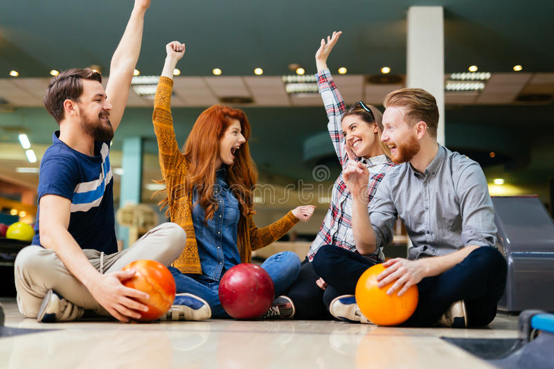 Cheerful friends bowling together stock photos