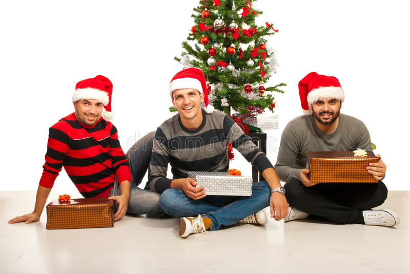 Cheerful friends with Christmas gifts. Cheerful friends standing in a row in front of Christmas tree stock photography
