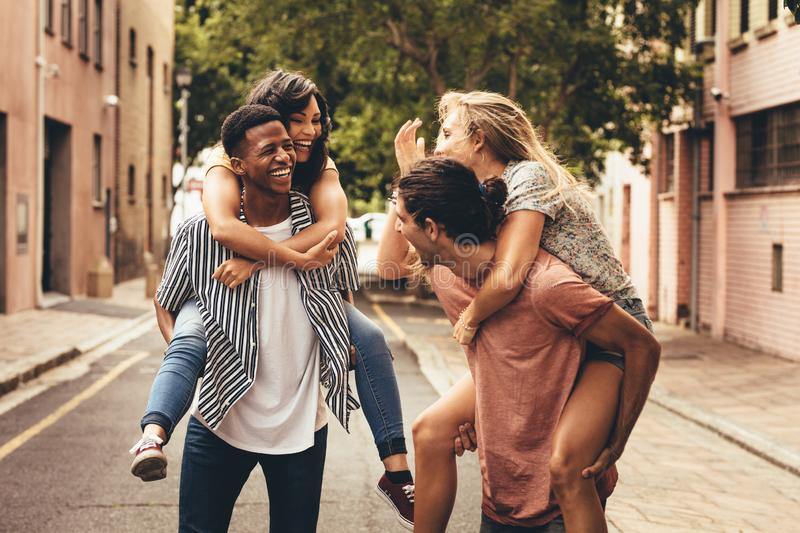 Cheerful friends enjoying outdoors. Two young men giving their girlfriends piggyback ride. Cheerful young friends enjoying outdoors on city street stock photography
