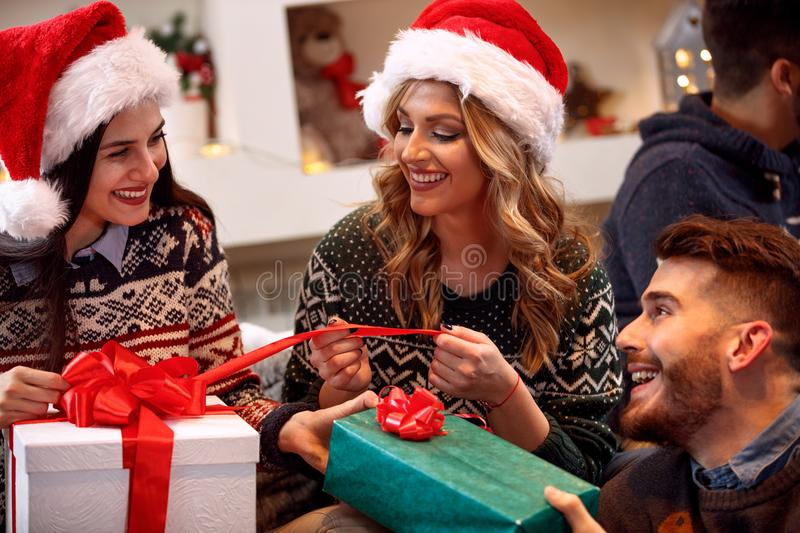 Friends exchanging presents at Christmas eve stock images