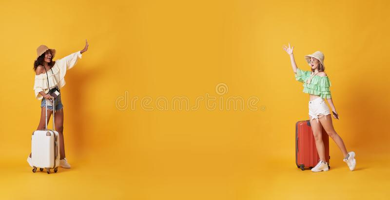 Cheerful friends greeting and meeting dressed in summer clothes standing with a suitcase and say hello at copy space isolated over. Yellow background royalty free stock images