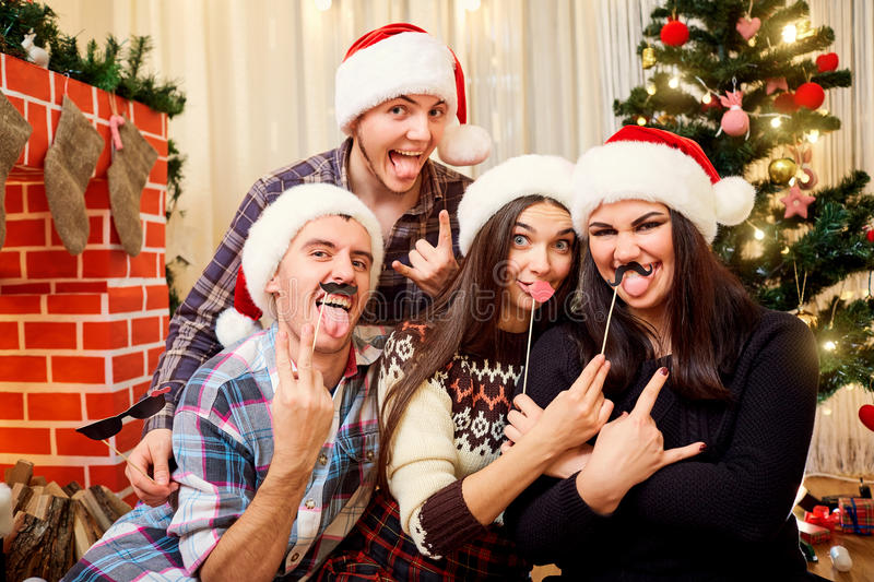 Cheerful friends in hats Santa Claus at Christmas, New Year laugh, have fun at the Christmas tree and fireplace. stock photos
