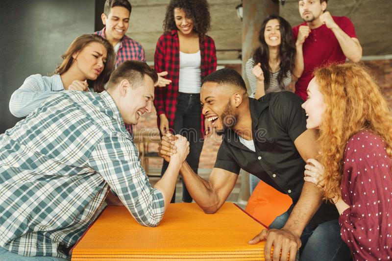 Cheerful friends having fun arm wrestling. Each other on party with friends royalty free stock photography
