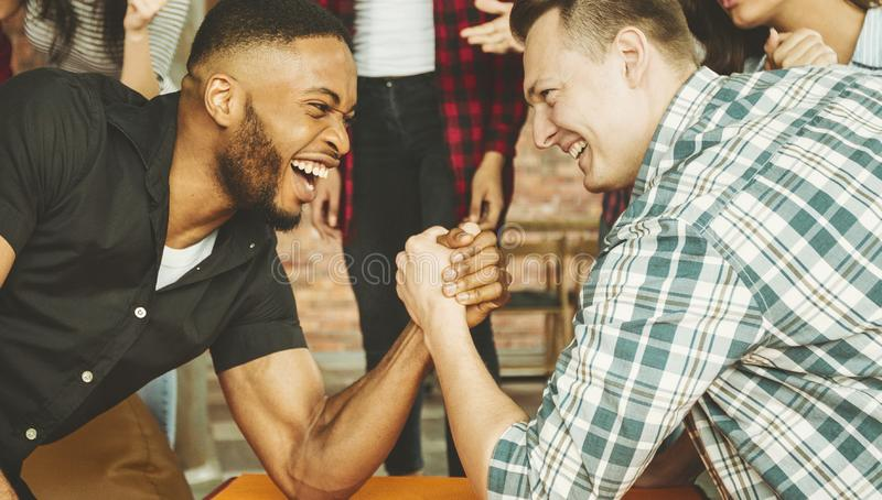 Cheerful friends having fun arm wrestling. Each other on party with friends stock image