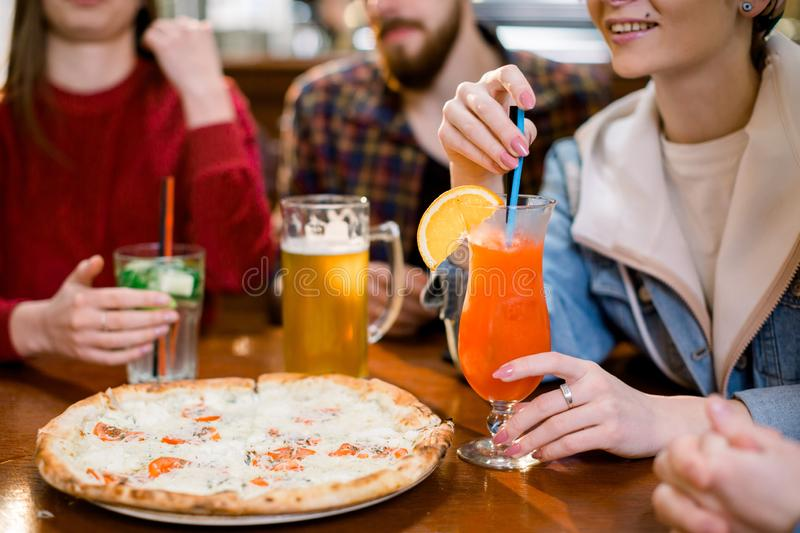 Cheerful friends having fun eating pizza and drinking beer and juice in pizzeria. Cropped image of hands holding glasses royalty free stock image